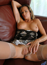 Slender tan milf spreads her pussy and stuffs her fingers deep inside