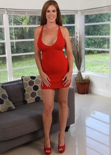 Busty MILF Ivy Secret slowly slips out of her tight red dress.