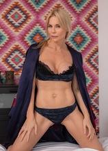 Blonde MILF Nadya Basinger exposes big fake tits and shaved pussy.