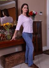 Mature brunette Nora Noir slips out of her blue jeans.