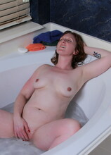 This naughty red mom loves playing with herself in the bathtub