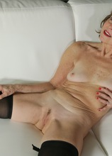 Mature redhead Amy D posing naked in only her black stockings.