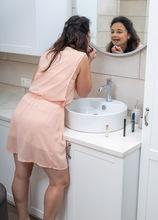 Sexy brunette MILF Anette Harper masturbates in the bathroom.