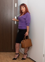 Older redhead Beau Diamonds spreads her pink stocking covered legs.