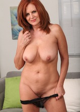 Mature redhead Andi James slowly strips naked on the sofa.