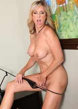 Busty cougar Jodi jams white dildo into her wet pussy.
