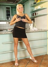 Blonde MILF Chrisy Bloom fingers her pussy in the kitchen.