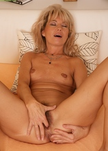Older bird Janet Darling slips fingers into her hairy twat.