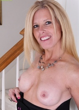 Busty mature Monique slides black dress off her tight body.