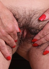 Older babe Bridget Calling exposes her hairy pussy.