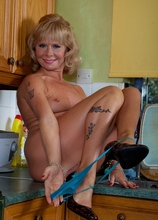 Housewife Cathy Oakley strips naked on kitchen counter.