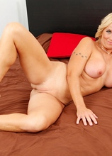 Busty blond cougar Dani Dare spreads her pussy lips.