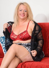 Busty and thick older amateur Erotica Ann toys her twat on the couch.