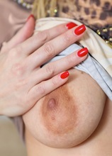 Mature babe Jenny Smith shows off her big areolas and shaved pussy.